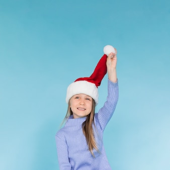 Cute little girl playing with a santa claus hat