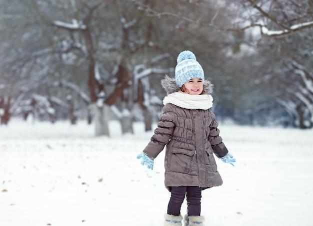 冬の公園で雪で遊ぶかわいい女の子