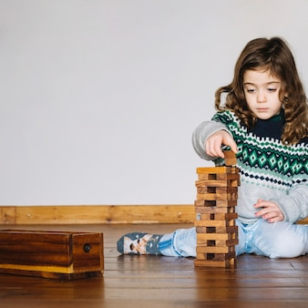 Cute little girl playing wooden block game