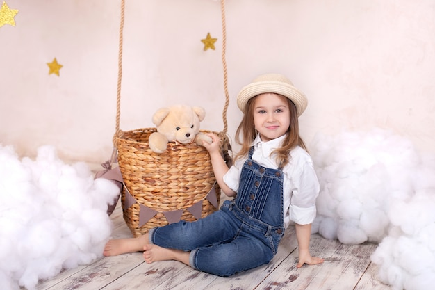 Cute little girl plays in a children room with a teddy bear and a balloon.
