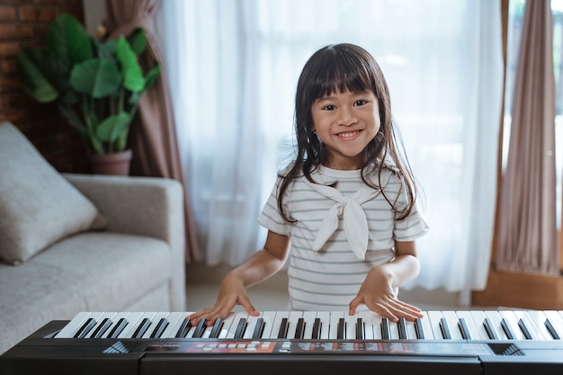 Cute little girl plays a keyboard instrument