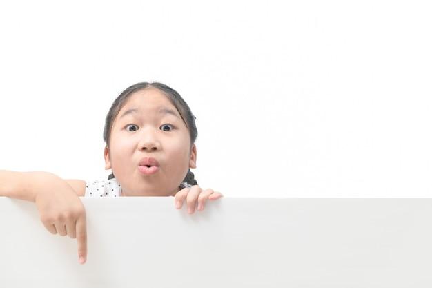 白い背景、バナー、入力テキストの概念の広告に分離された空白の看板を指すかわいい女の子。
