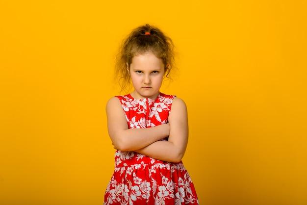 黄色の背景に悲しいポーズかわいい女の子