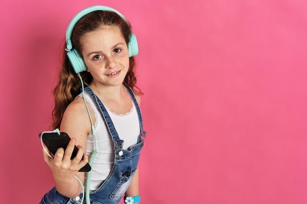 Bambina carina in posa con un telefono e cuffie su uno sfondo rosa