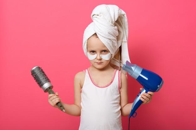 Милая маленькая девочка позирует с круглой щеткой и феном в руках