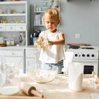 Милая маленькая девочка готовит тесто