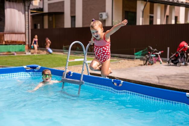 Cute little girl preparing to jump into blue water, having fun in the pool