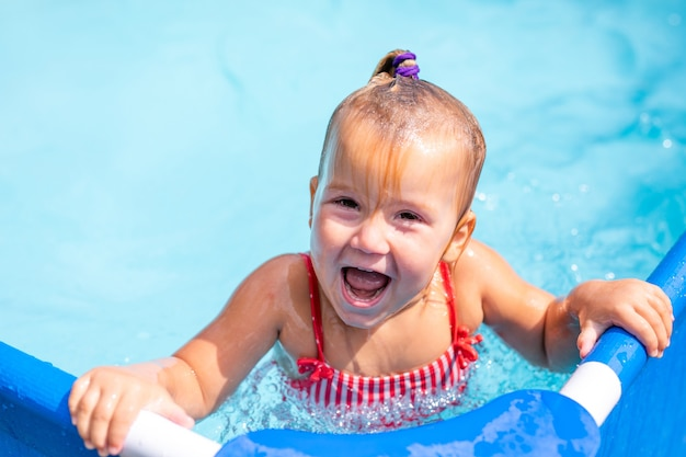 Cute little girl preparing to jump into blue water
