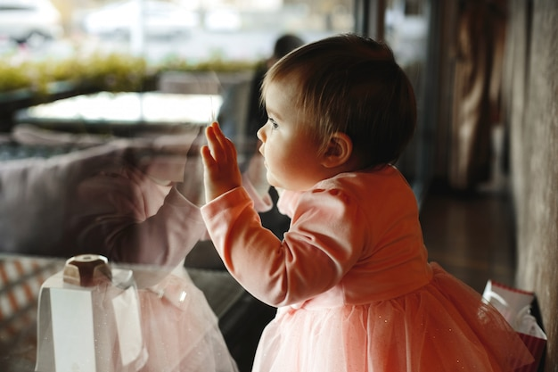 Cute little girl puts her hands on the window