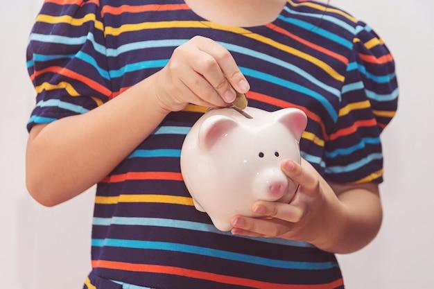 Cute little girl putting coin into piggy bank