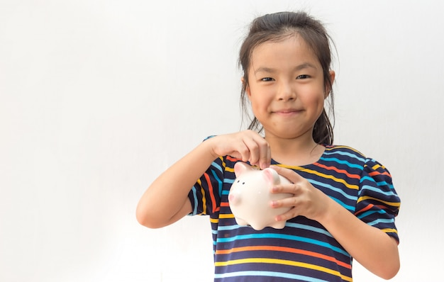 Cute little girl putting coin into piggy bank