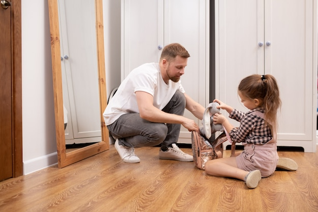 Cute little girl putting soft toy into rucksack while father helping her to pack things for school on the floor of corridor in the morning