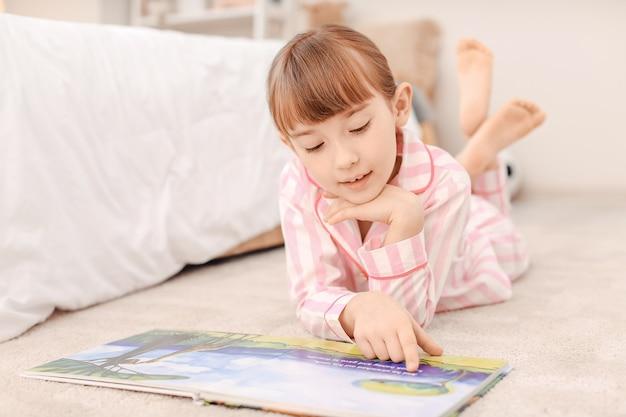 Милая маленькая девочка читает сказку на ночь дома