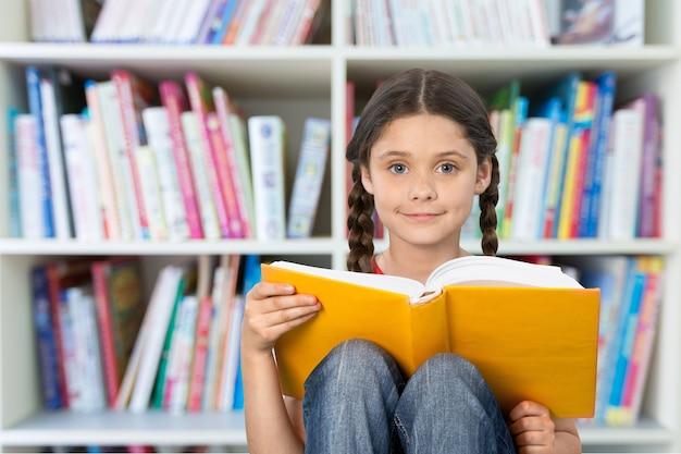 Cute little girl reading big yellow book