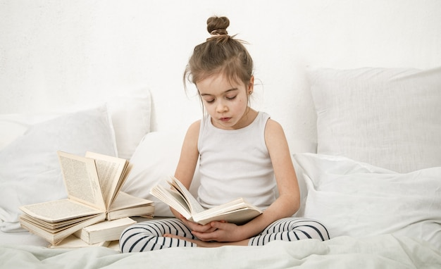 Bambina sveglia che legge un libro sul letto in camera da letto. il concetto di educazione e valori familiari.