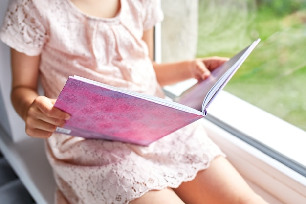Cute little girl reading book at home, at windowsill, child studying at home, quarantine, stay home, life style.