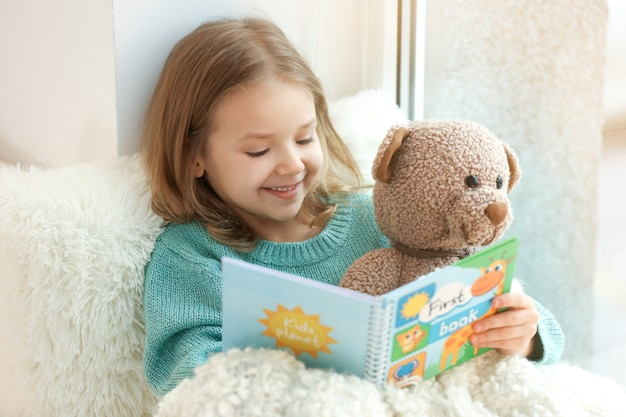 집에서 창틀에 앉아있는 동안 책을 읽는 귀여운 소녀