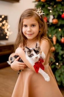 Милая маленькая девочка получила в подарок котенка на новый год