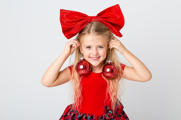 A cute little girl in a red dress and bow on her head holding christmas tree toys. white background, space for text