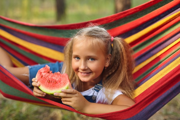 森の色のハンモックで休んで、新鮮なスイカを食べるかわいい女の子