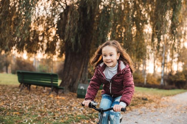 일몰에 대 한 야외 공원에서 자전거를 타고 귀여운 소녀.