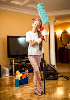Cute little girl in rubber gloves posing with mop at living room