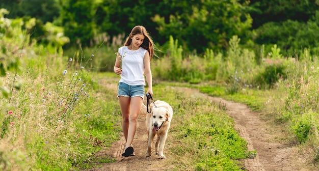 夏の地上道路で愛らしい犬と一緒に走っているかわいい女の子