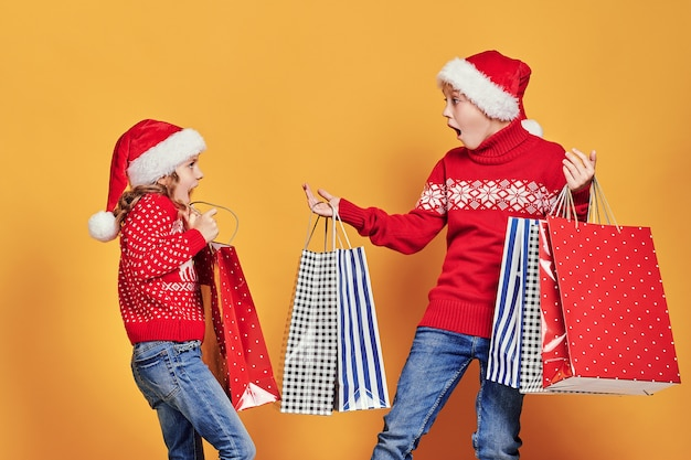 Cute little girl in santa hat hanging shopping bag with christmas gifts on hand of astonished boy during holiday celebration against yellow background