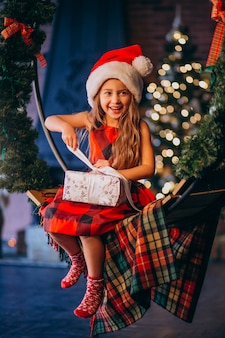 Cute little girl in santa hat unpacking christmas present