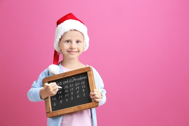 Cute little girl in santa hat with chalkboard counting days until christmas, on color wall