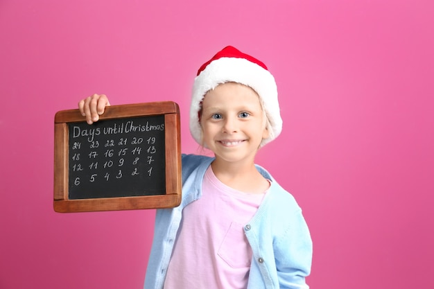 Cute little girl in santa hat with chalkboard counting days until christmas