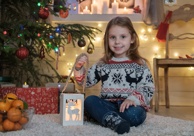 Cute little girl in a scandinavian sweater at the christmas tree. the concept of a family celebration of christmas and new year