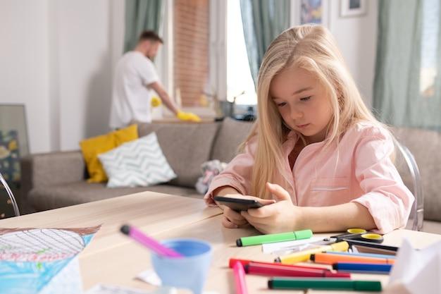 Милая маленькая девочка просматривает фотографии в смартфоне, сидя за столом в гостиной на фоне своего отца, выполняющего домашние дела