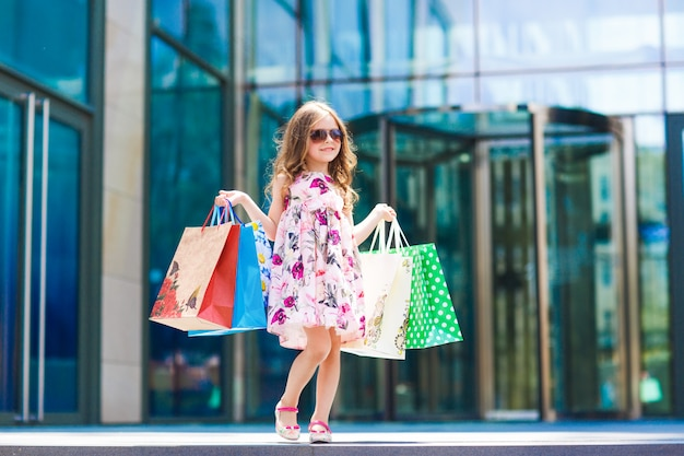 Cute little girl on shopping, portrait of a kid with shopping bags, shopping, girl.