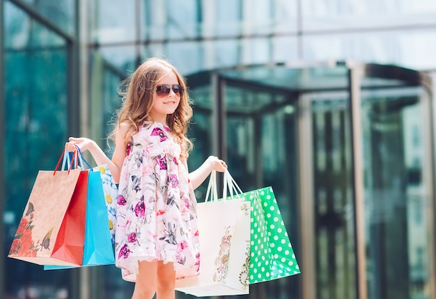 Cute little girl on shopping. portrait of a kid with shopping bags. shopping. girl.