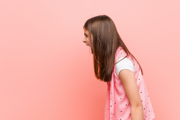 Cute little girl shouting towards a copy space