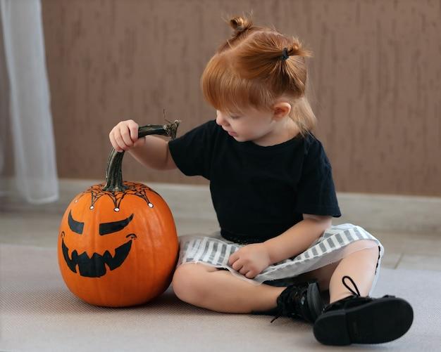 귀여운 소녀는 휴일을 기대하며 할로윈에 색칠된 호박을 바라보고 앉아 있다