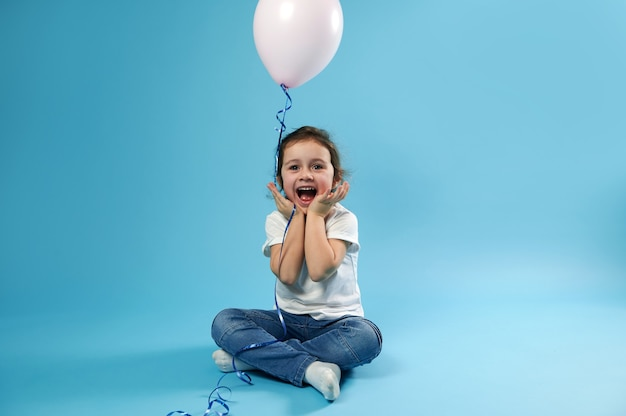 A cute little girl sits on a blue surface with a balloon in her hands and rejoices in the surprise of her birthday expression of joyful emotions