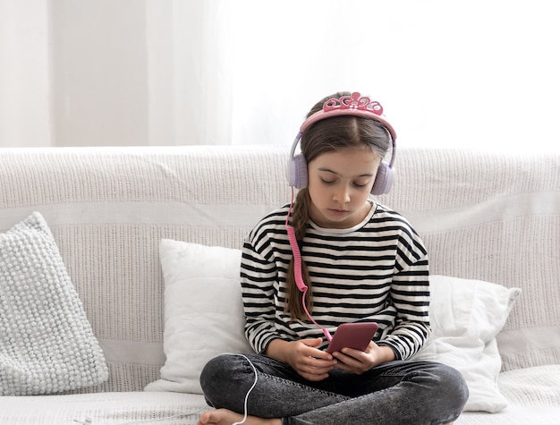 A cute little girl sits at home on the couch and listens to music with headphones