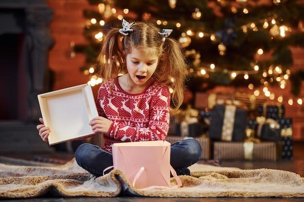 かわいい女の子は、装飾されたクリスマスルームのオープニングギフトボックスに座っています。