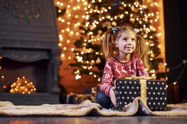 かわいい女の子は、ギフトボックスで飾られたクリスマスの部屋に座っています。