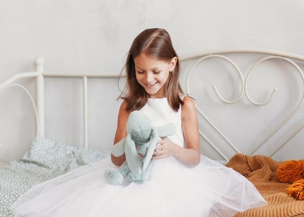 귀여운 소녀는 장난감과 미소로 침대에 앉아