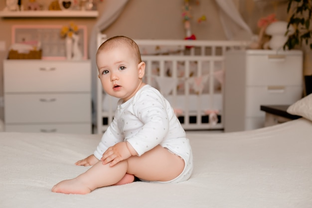 Милая маленькая девочка сидит на кровати