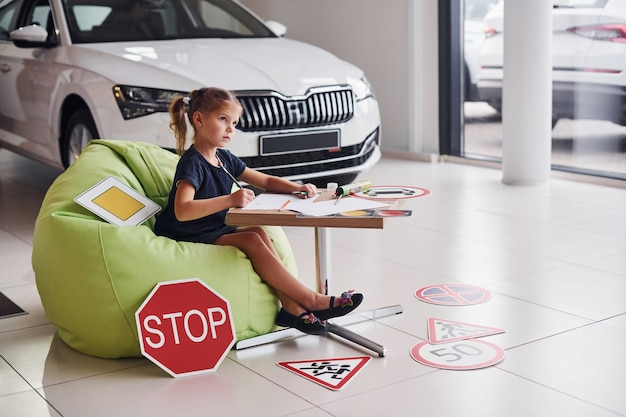Cute little girl sits on the soft green chair by the table with pencil and paper sheets. near modern automobile and road signs on the floor.