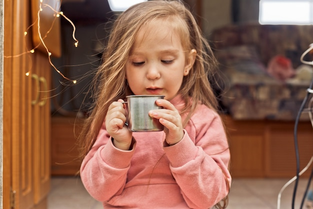 Cute little girl sits on the steps of a travel trailer and drinks hot chocolate with marshmallows