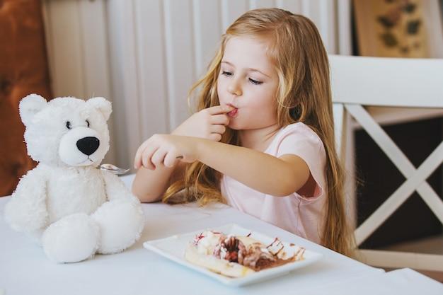 Милая маленькая девочка сидит за столиком в кафе и кормит любимого игрушечного медведя мороженым
