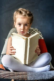 Bambina sveglia che si siede su una bella sedia con un libro in mano, il concetto di educazione e vita scolastica