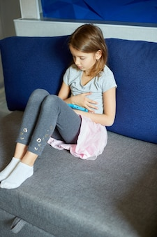 Cute little girl sitting on couch, kid addicted to technology, enjoying playing online game on digital tablet computer, using applications, web surfing information at home,