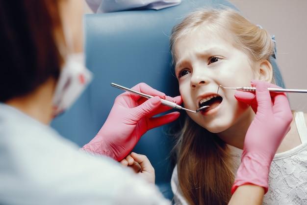 Cute little girl sitting in the dentist's office