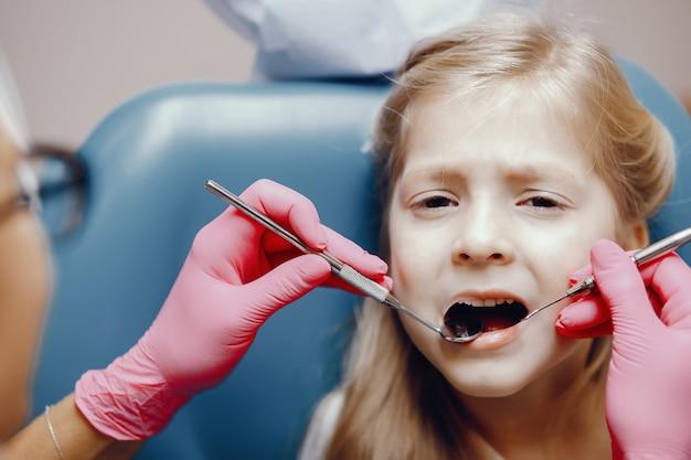 Bambina sveglia che si siede nell'ufficio del dentista